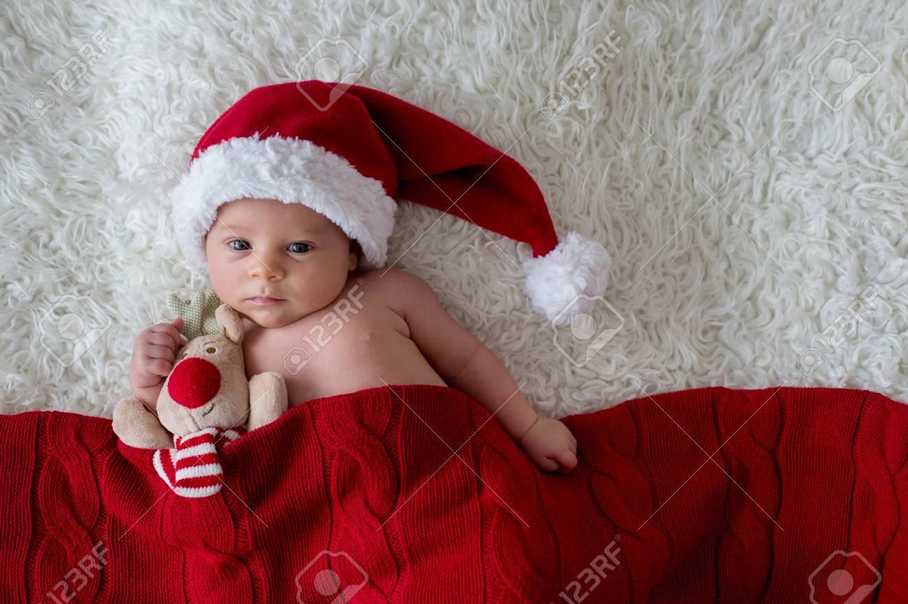 558efdca1 Little newborn baby boy, wearing Santa hat and pants, holding..