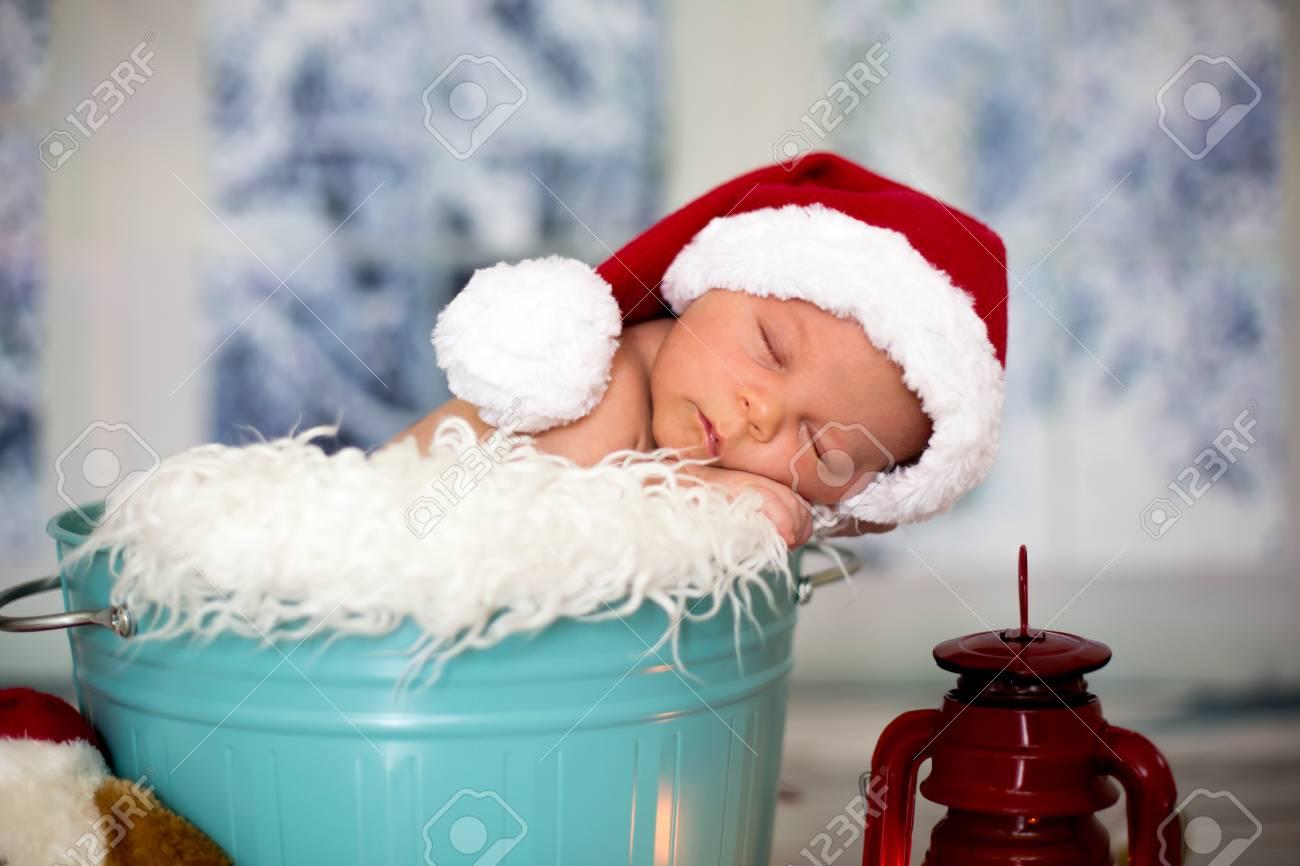 Portrait of a newborn baby boyl wearing christmas hat sleeping in a blue