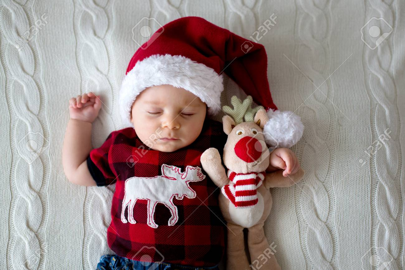 bab13cfd8 Little sleeping newborn baby boy, wearing Santa hat and jeans, holding toy  Stock Photo