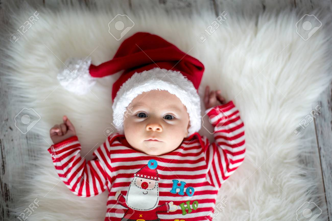 Christmas portrait of cute little newborn baby boy dressed in christmas clothes and wearing santa