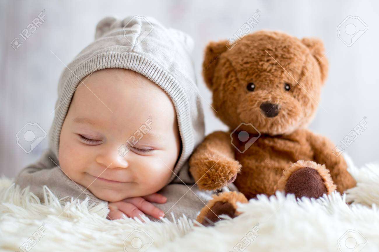 Sweet Baby Boy In Bear Overall Sleeping In Bed With Teddy Bear
