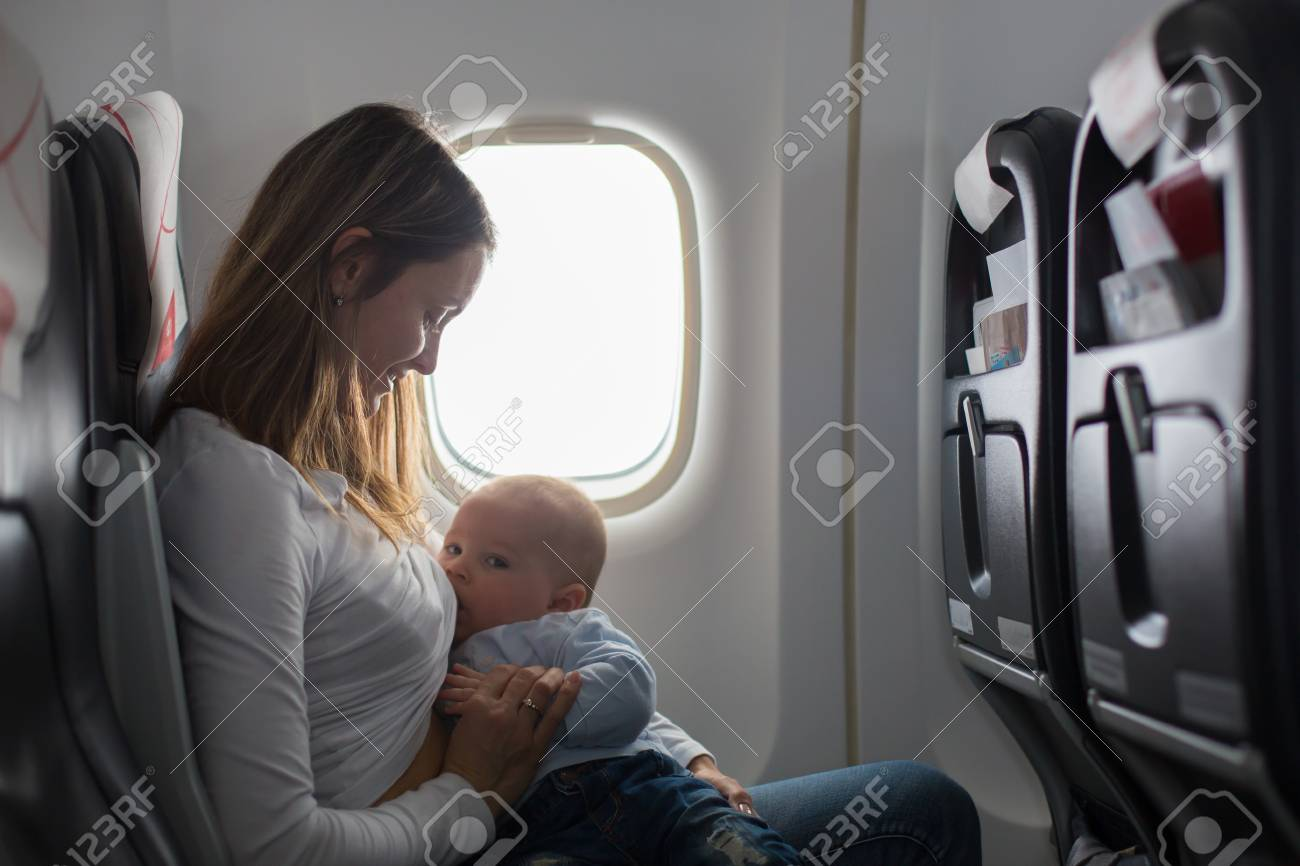 Young mom, playing and breastfeeding her toddler boy on board of aircraft, going on holiday - 99247562