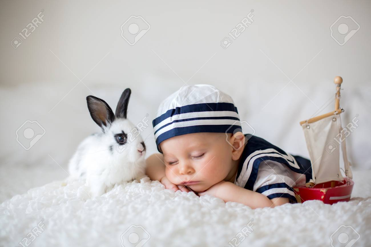 cute baby boy, dressed in sailor clothes, sleeping with wooden