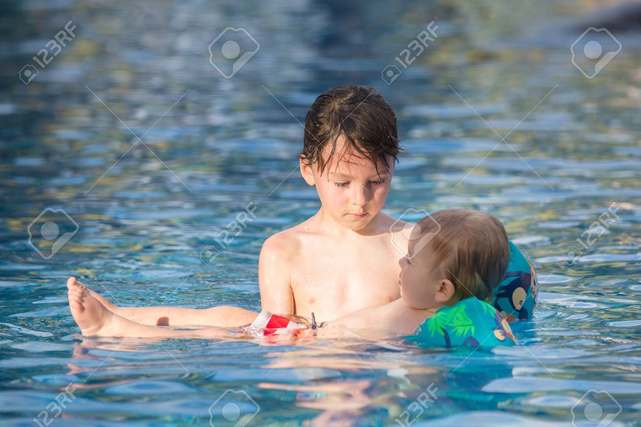Adorable happy little child, toddler boy, having fun relaxing and playing with his older brother in a pool on sunny day during summer vacation in resort - 120400389