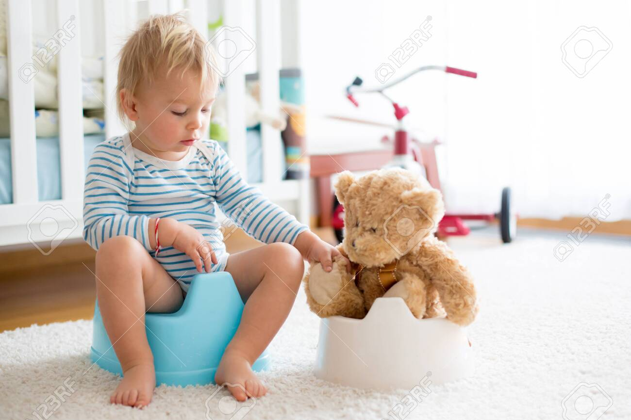 Cute toddler boy, potty training, playing with his teddy bear on potty - 124260330