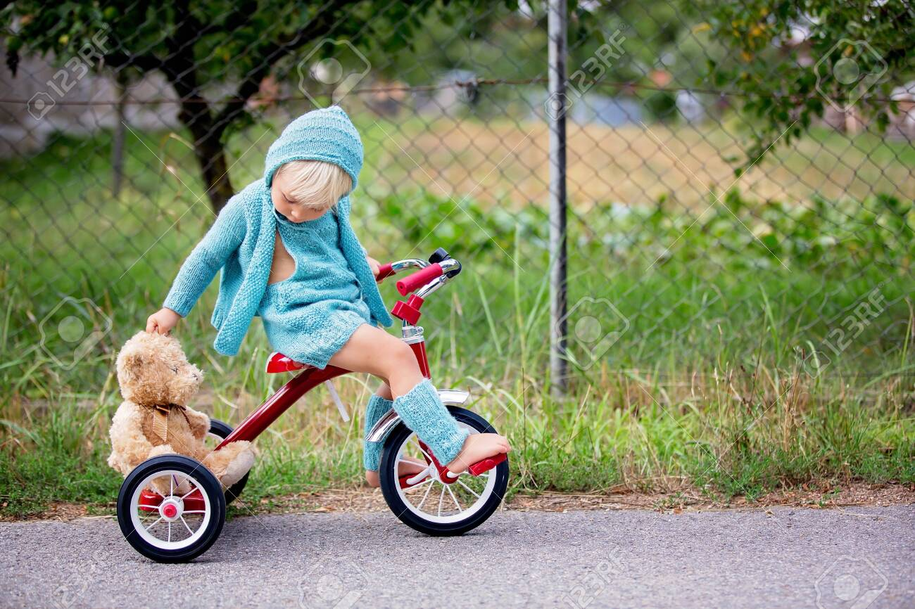 Adorable toddler boy with knitted outfit, riding tricycle on a quiet village street, summertime - 129399124