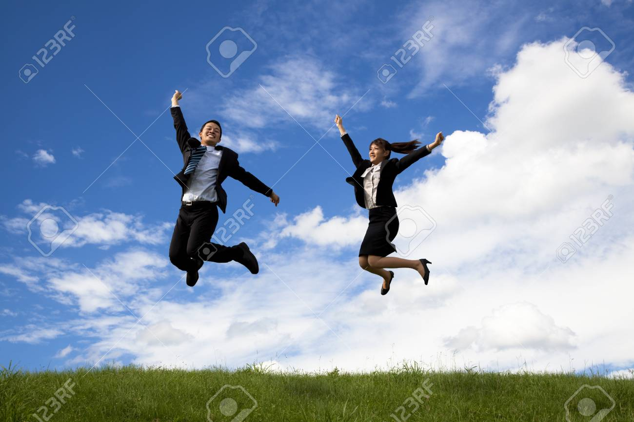 Happy Businessman and businesswoman jumping on a green meadow Stock Photo - 8331856