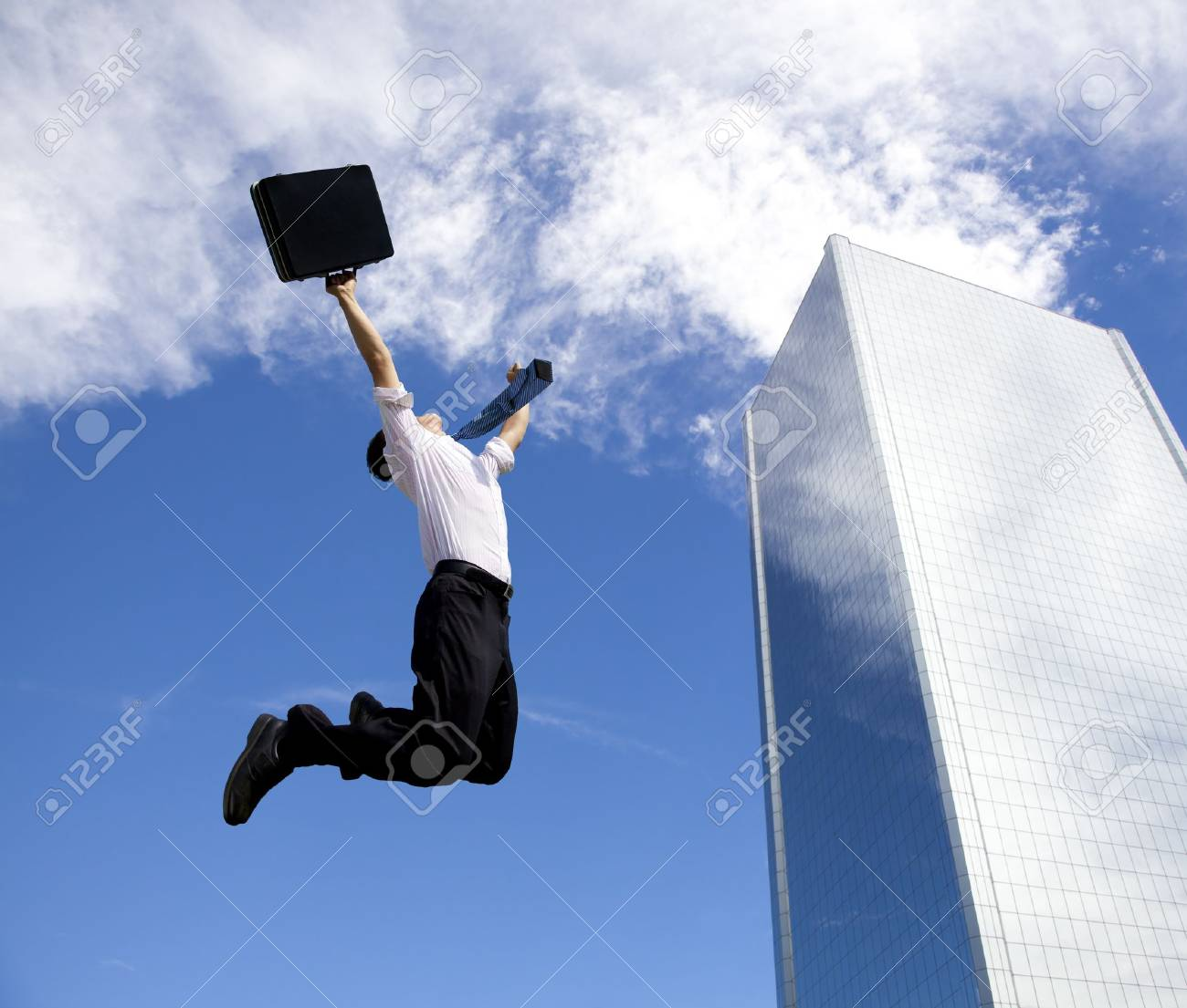 happy businessman jumping in front of a building - 11332036