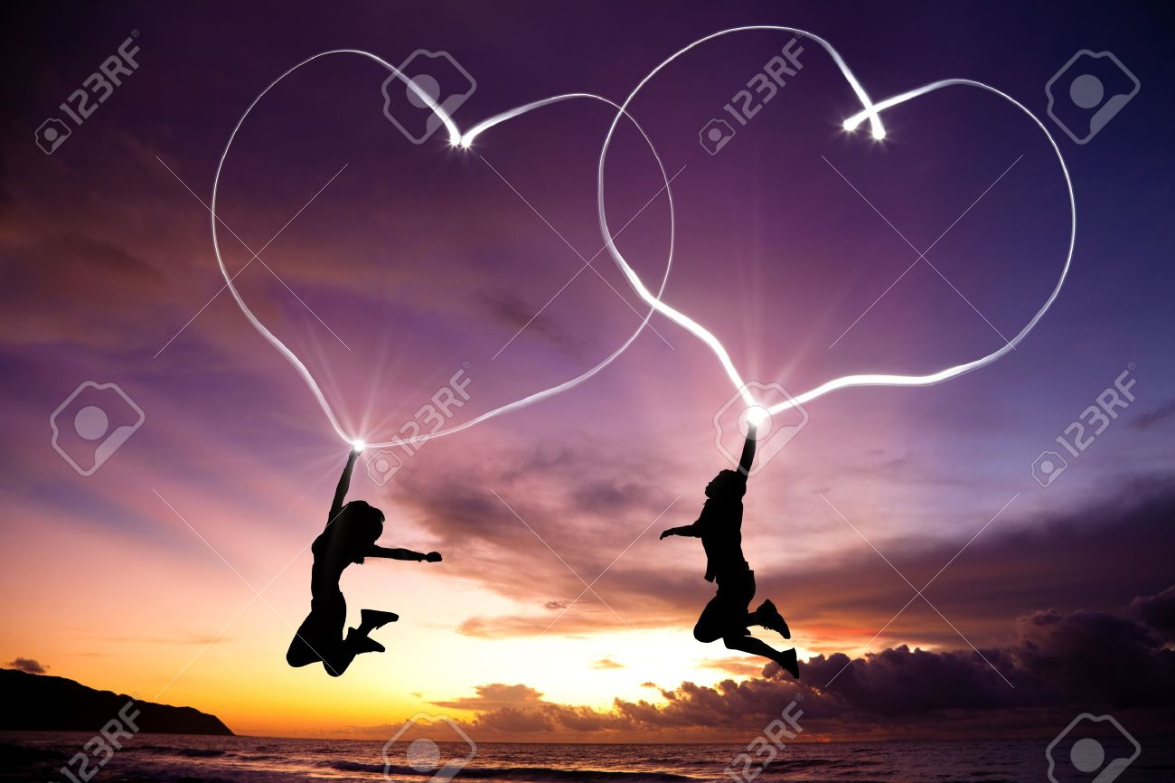 young couple jumping and drawing connected hearts by flashlight in the air on the beach before sunrise Stock Photo - 11567997