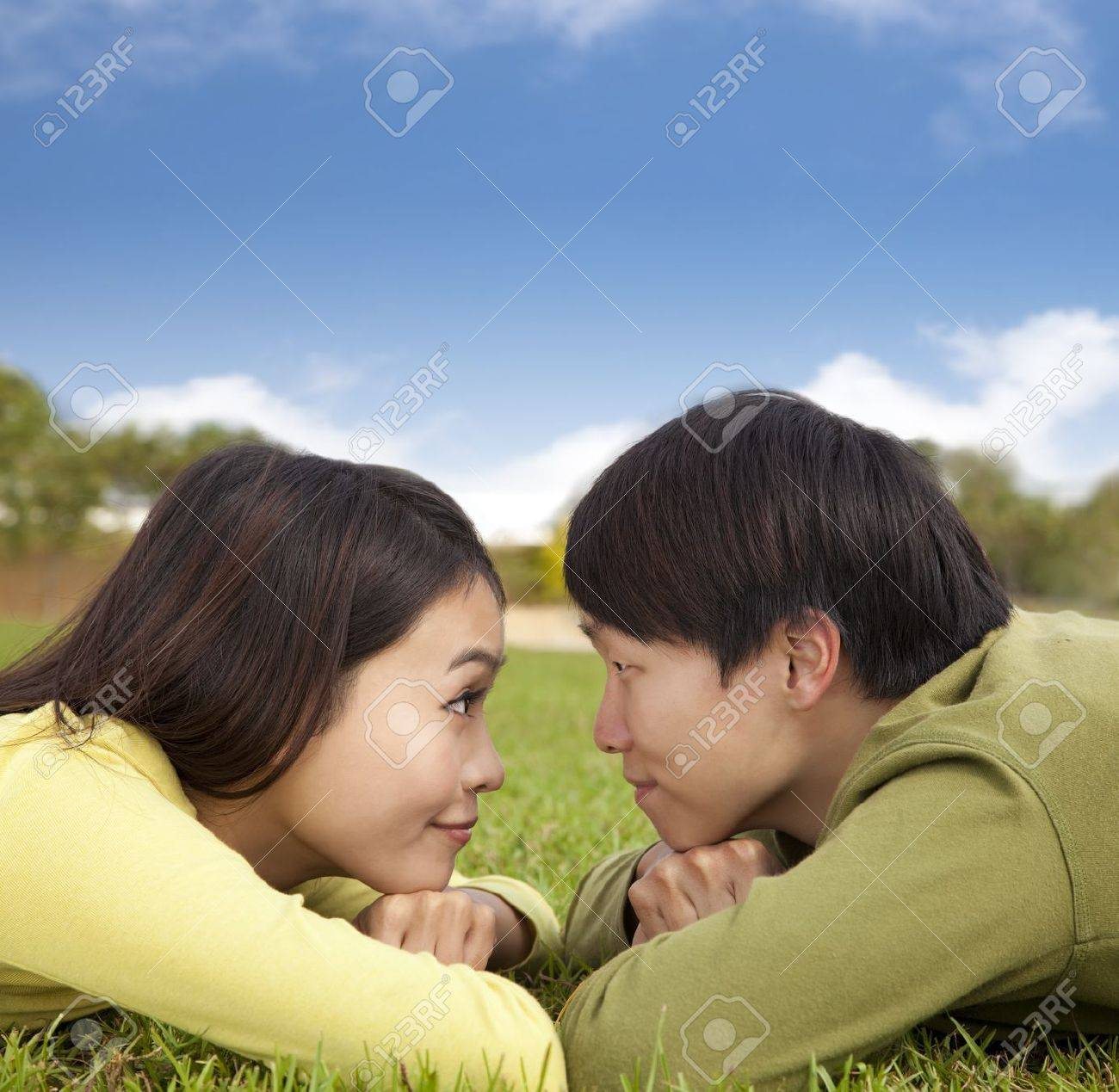 Happy asian couple lying on the grass with cloud background Stock Photo - 11568024