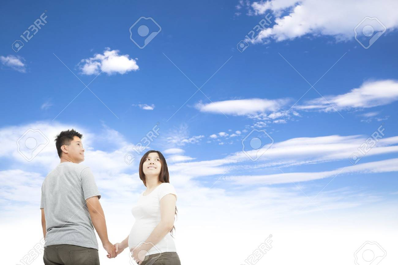 husband holding pregnant wife's hand and cloud background Stock Photo - 14742212