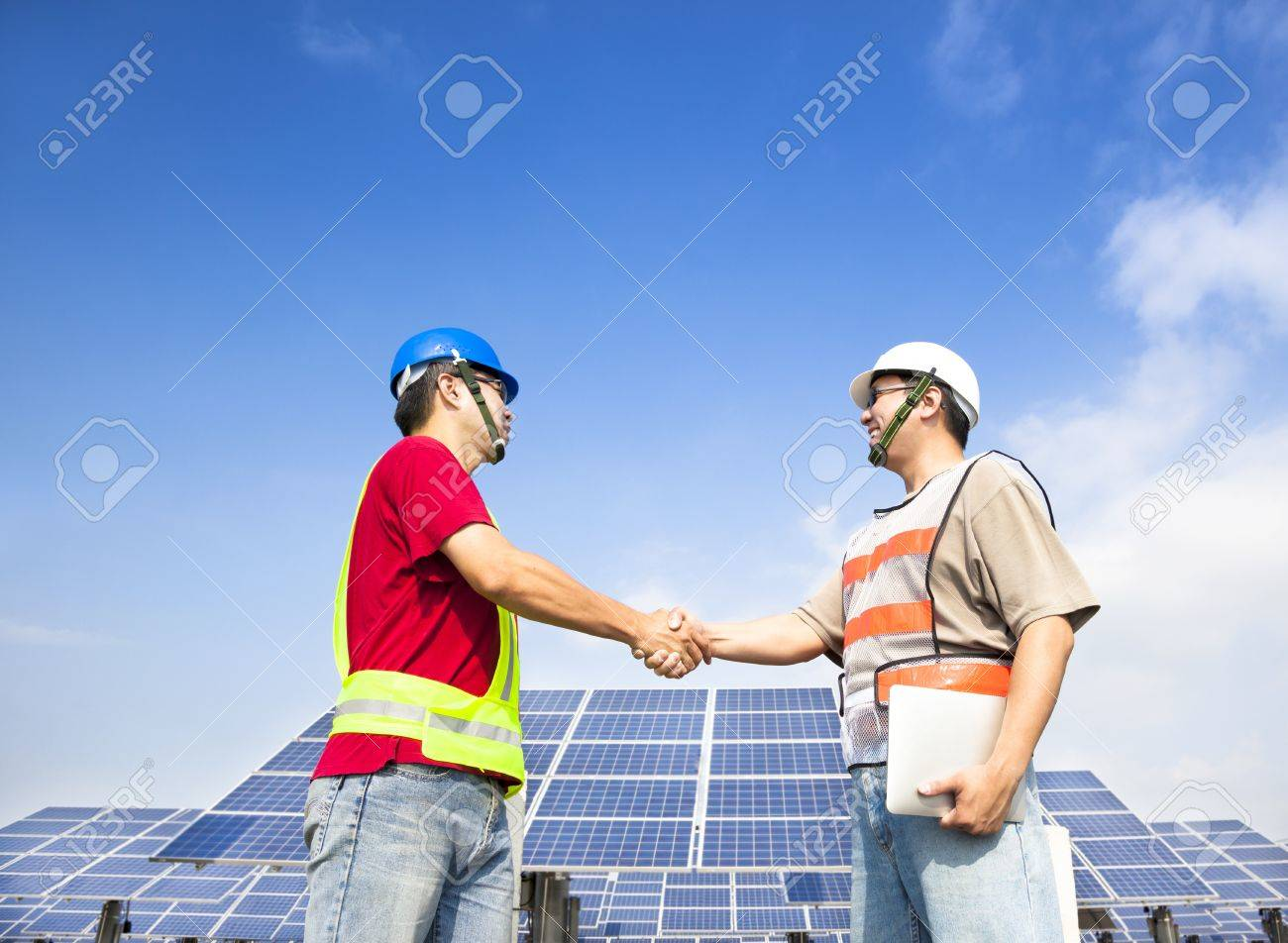 two engineers handshaking  before large solar power station Stock Photo - 16276299