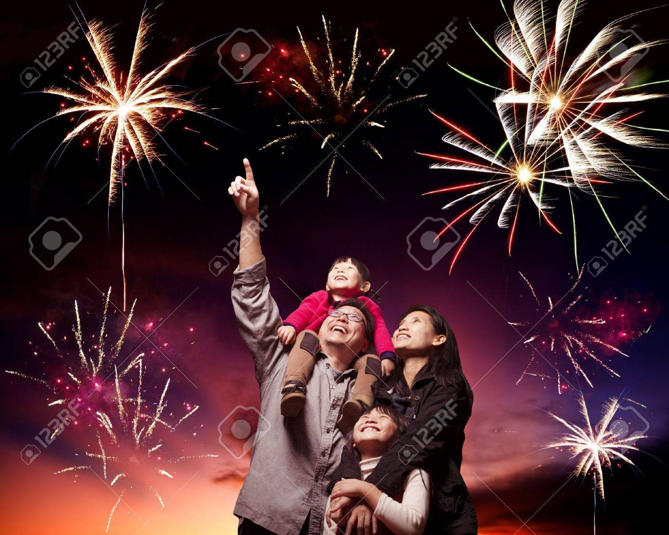 happy family looking fireworks in the evening sky stock photo