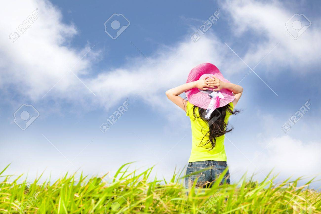 young woman stand in the grass field watching the cloud - 19359556