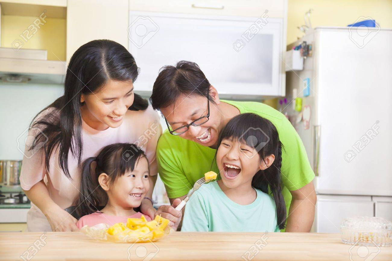 Happy family in kitchen - Happy Family And Daughter Eating Fruits In The Kitchen Stock Photo 22110743