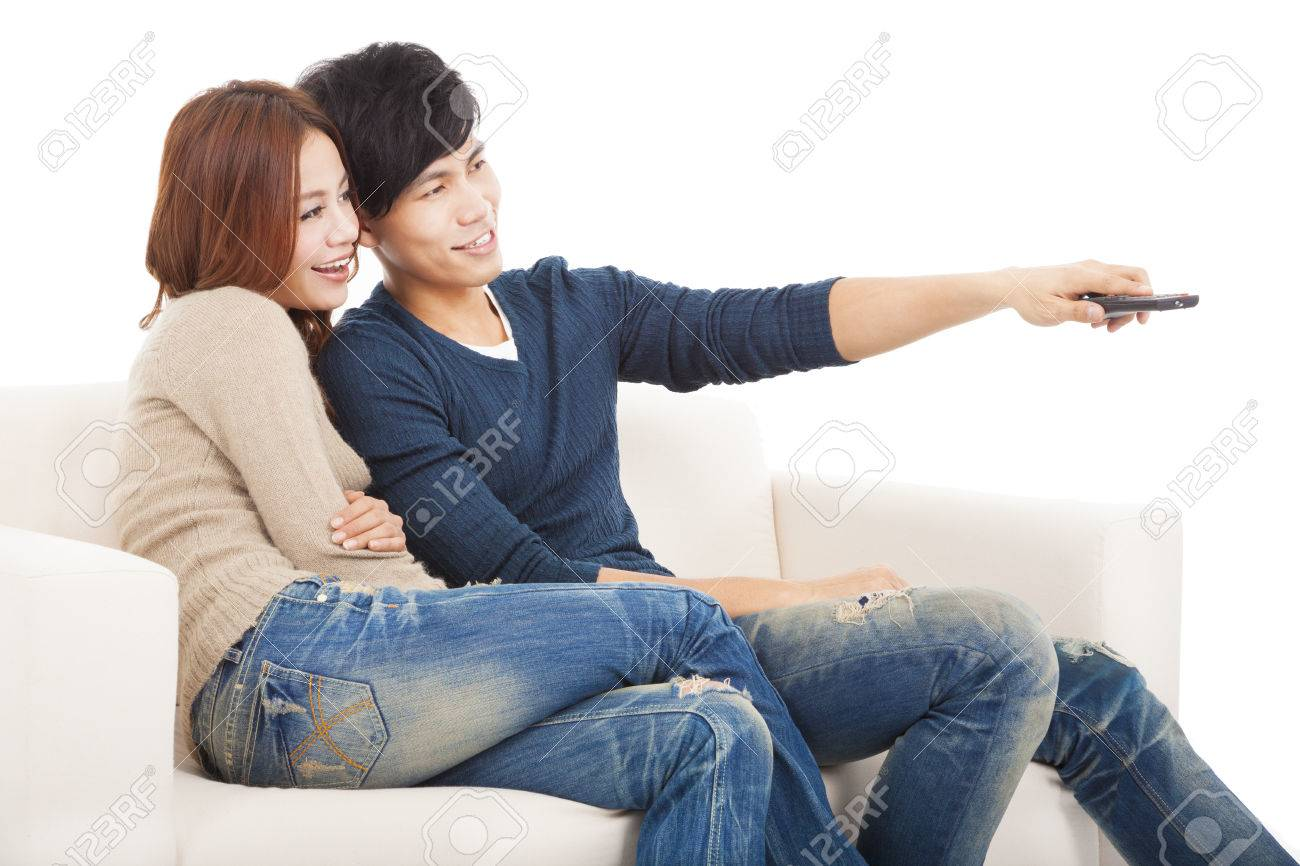 young couple on sofa watching TV with remote control Stock Photo - 24232073
