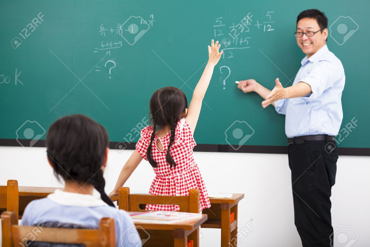 Teacher Asking Question With Children In Classroom Stock Photo ...