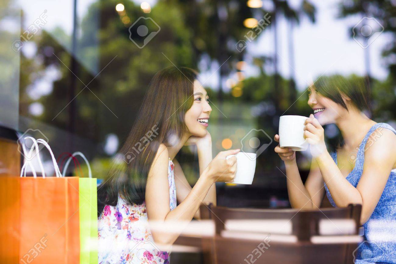 two young woman chatting in a coffee shop Stock Photo - 43936217