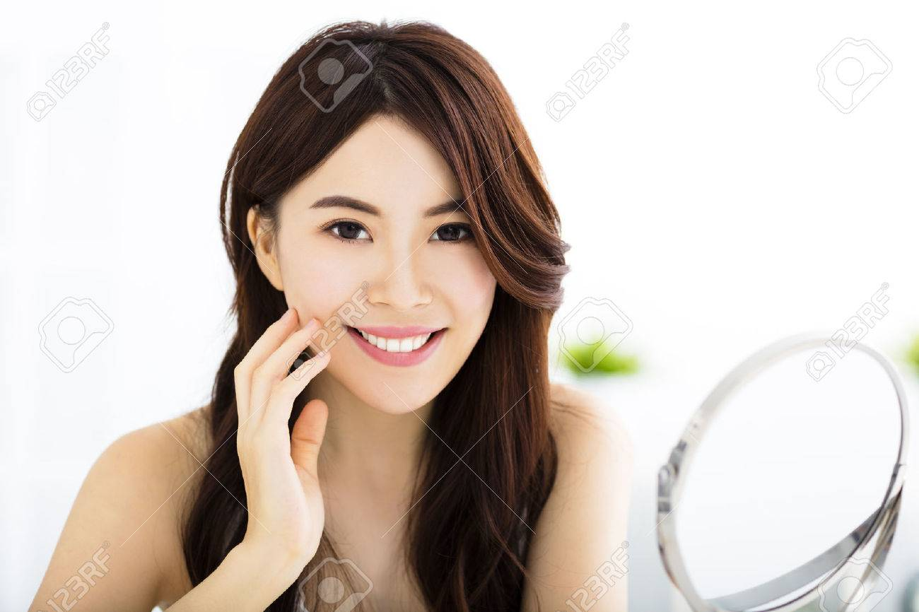 Happy young woman  looking on mirror Stock Photo - 44191752