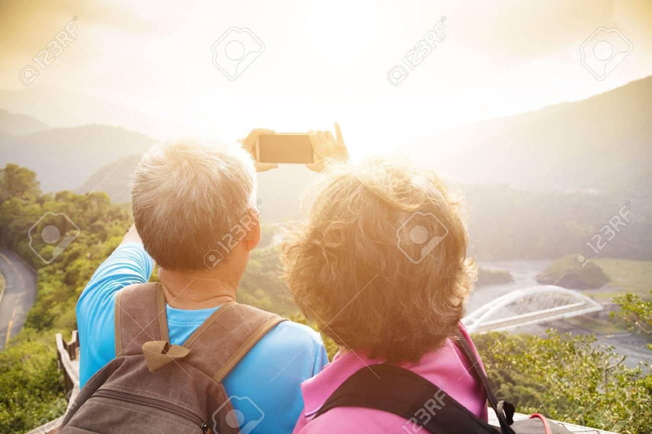 happy Senior couple hiking on mountains and taking selfies Stock Photo - 48616426