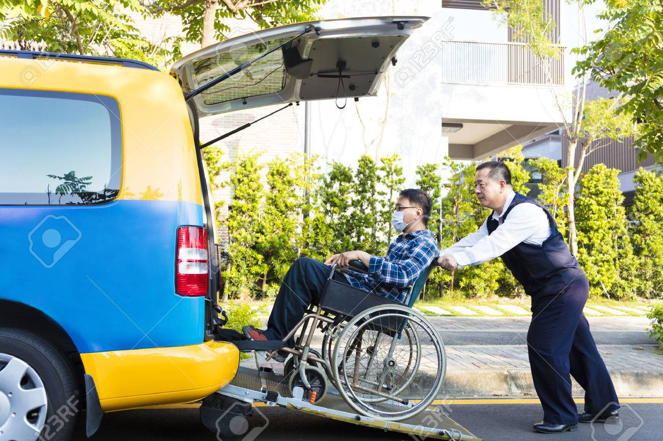 driver helping man on wheelchair getting into taxi Stock Photo - 49363953