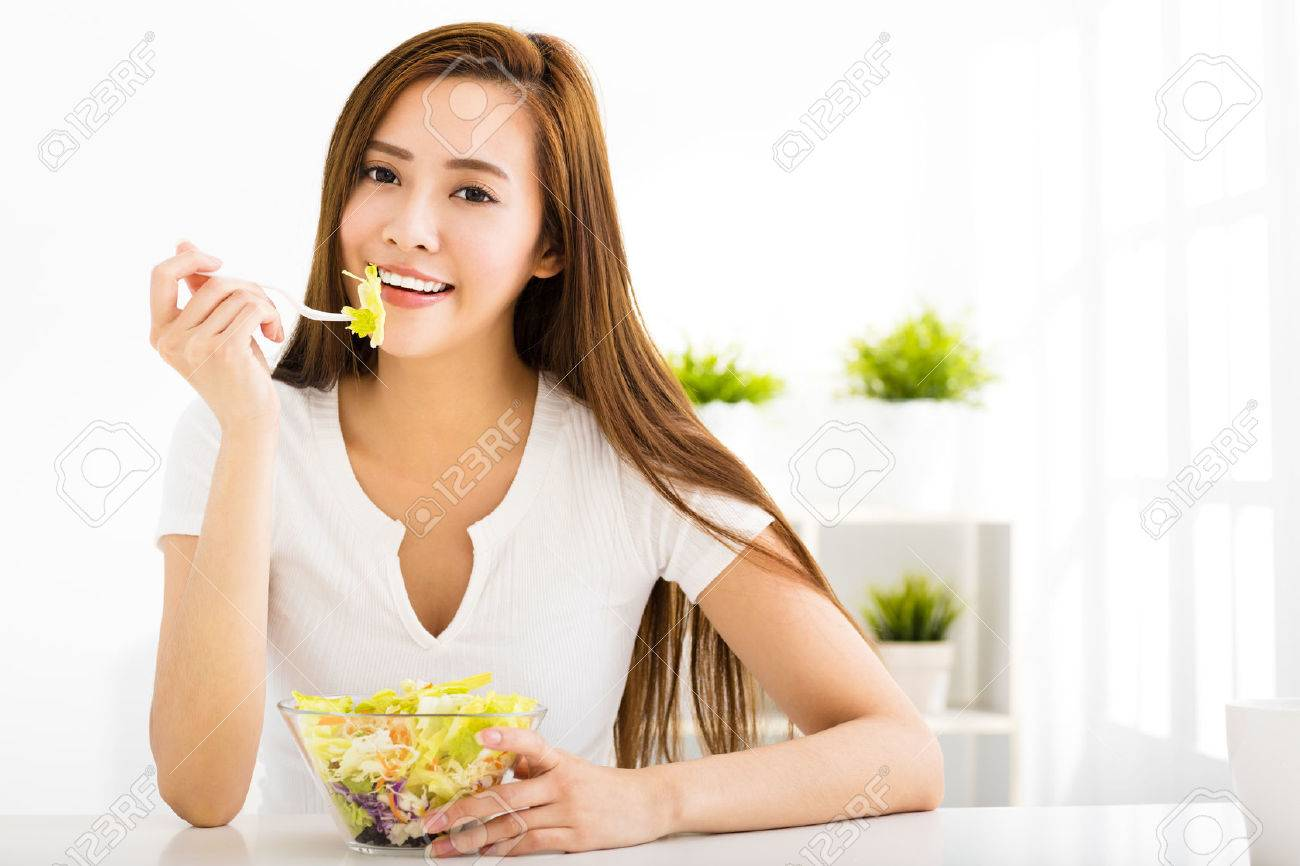 beautiful young woman eating healthy food - 50480583