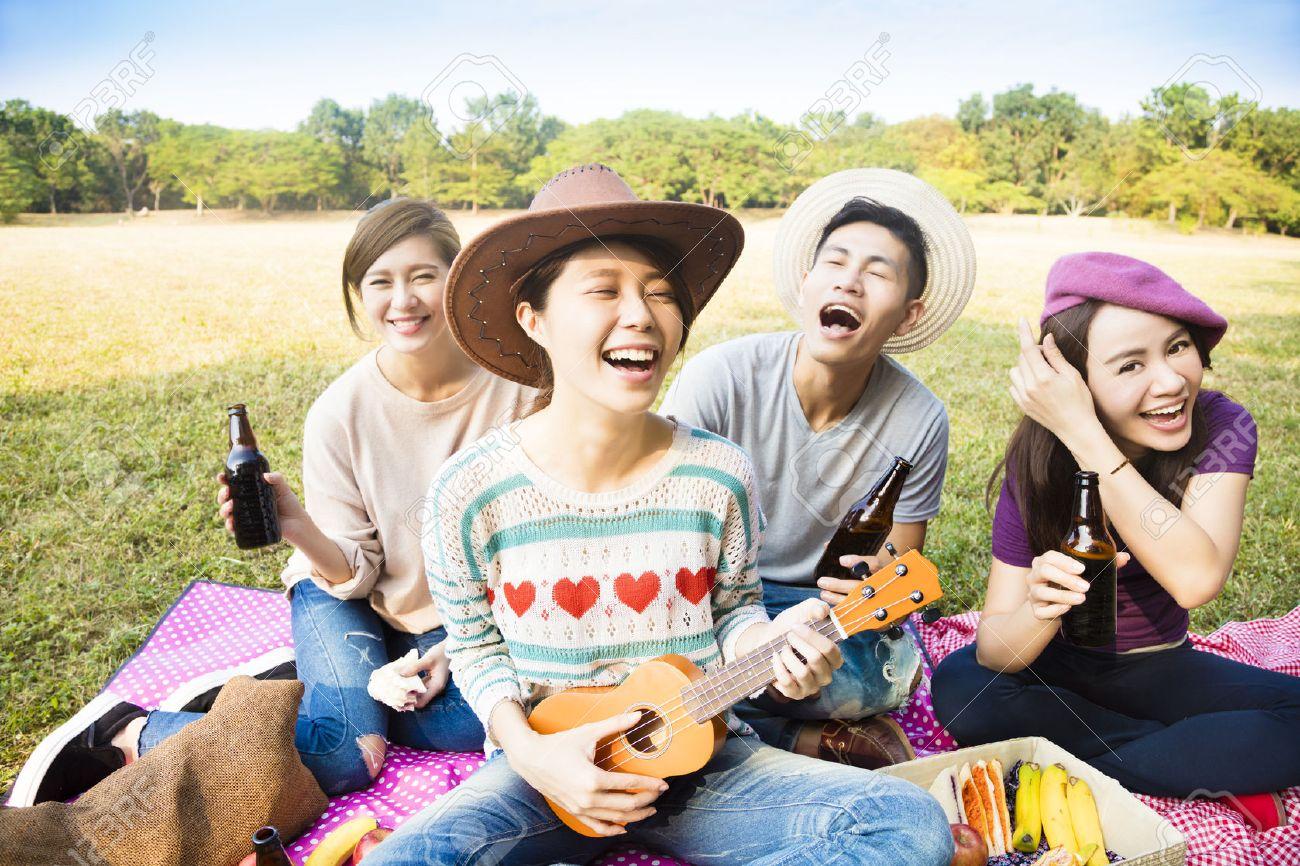 happy young friends enjoying picnic and playing ukulele - 50480630