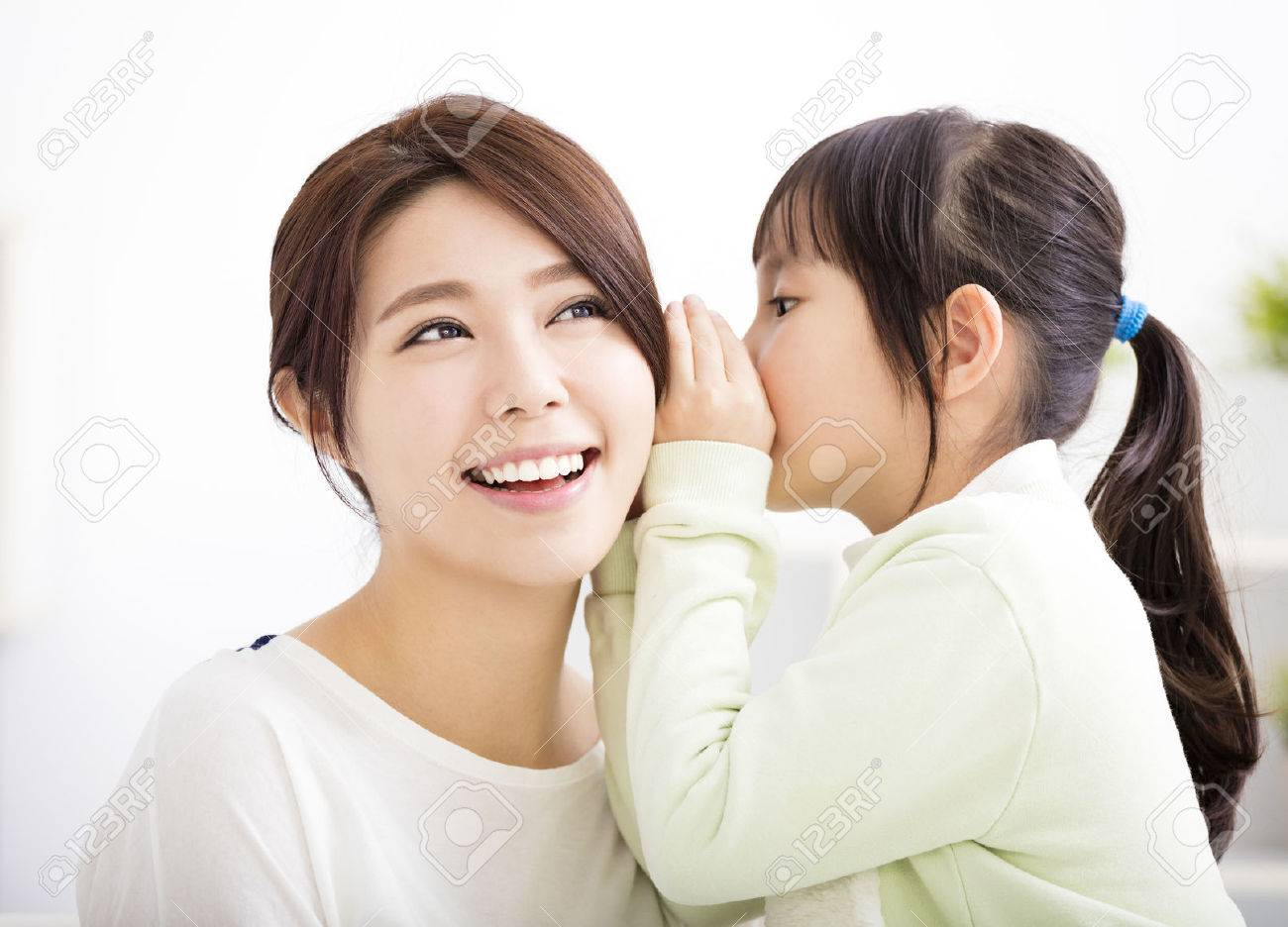 mother and daughter whispering gossip - 52256008