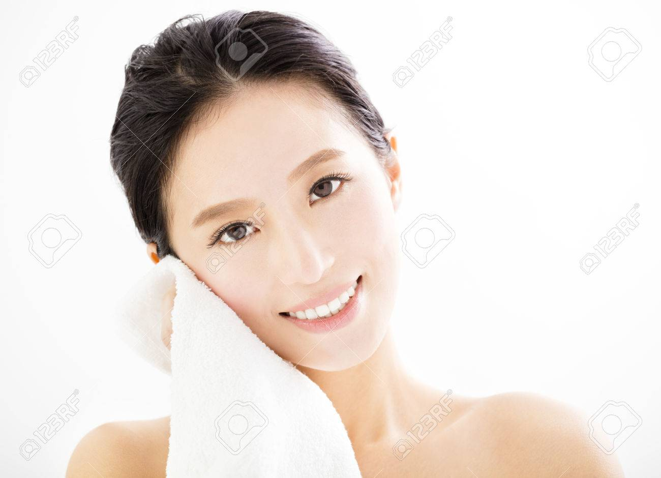 young woman cleaning her face with towel - 53696986