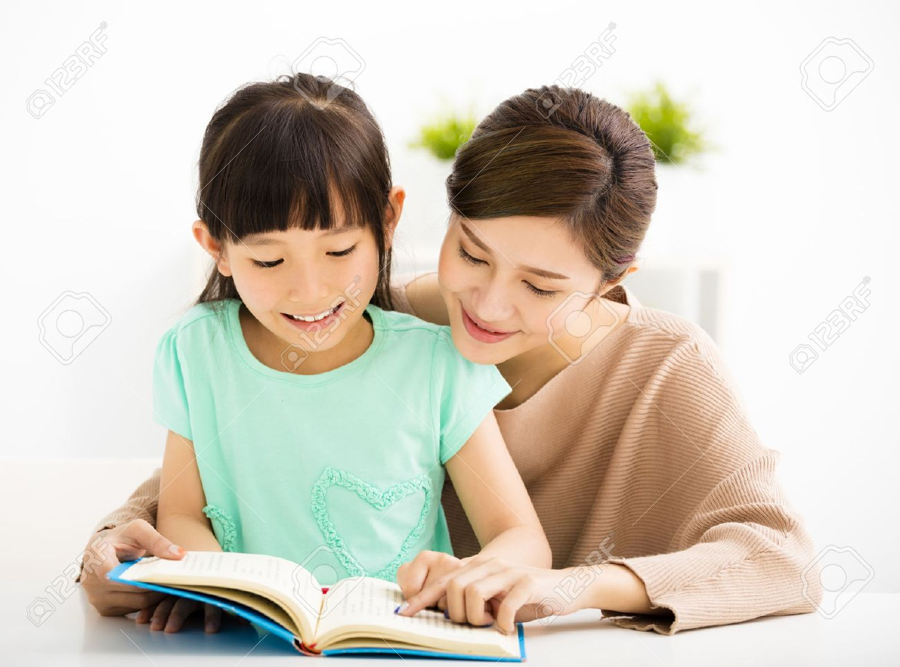 happy Little girl looking at book with her mother - 53697005