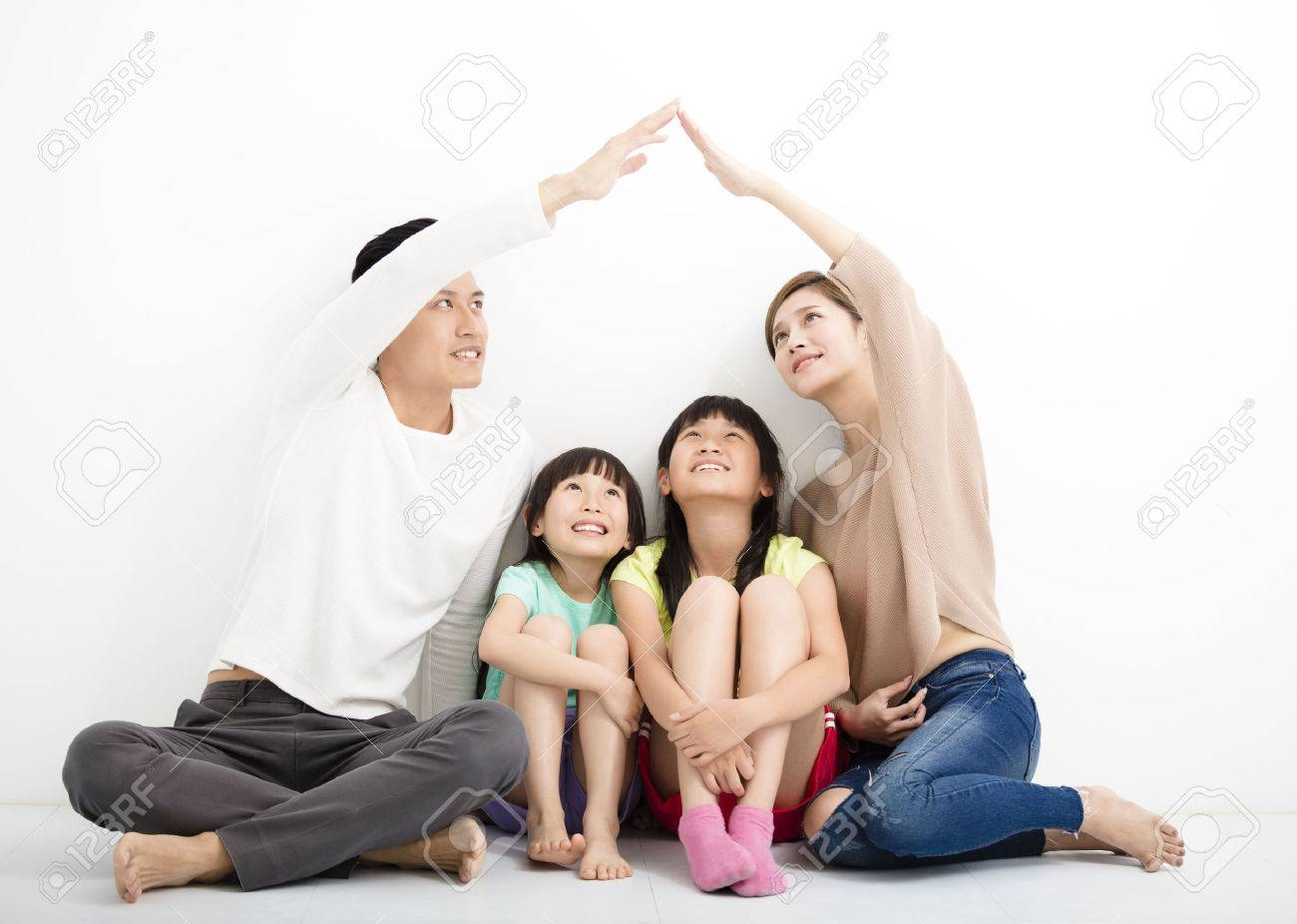 happy family sitting together and making the home sign Stock Photo - 54004106