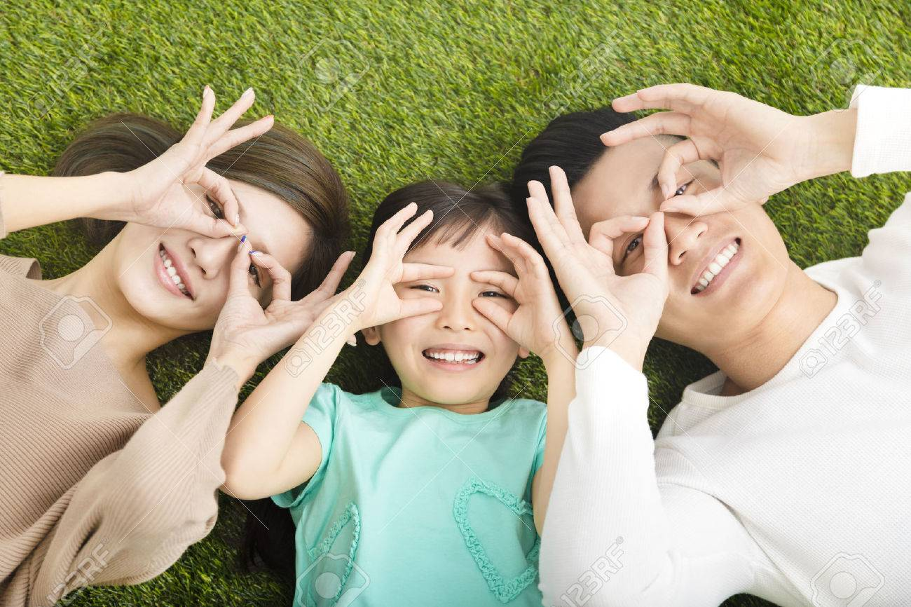 top view of Happy Young Family lying on the grass - 54131913