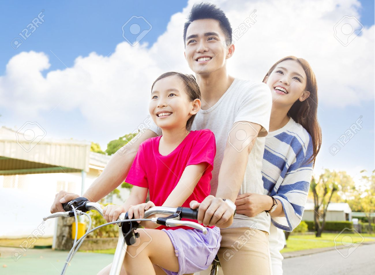 Happy asian family having fun in park with bicycle Stock Photo - 56086044