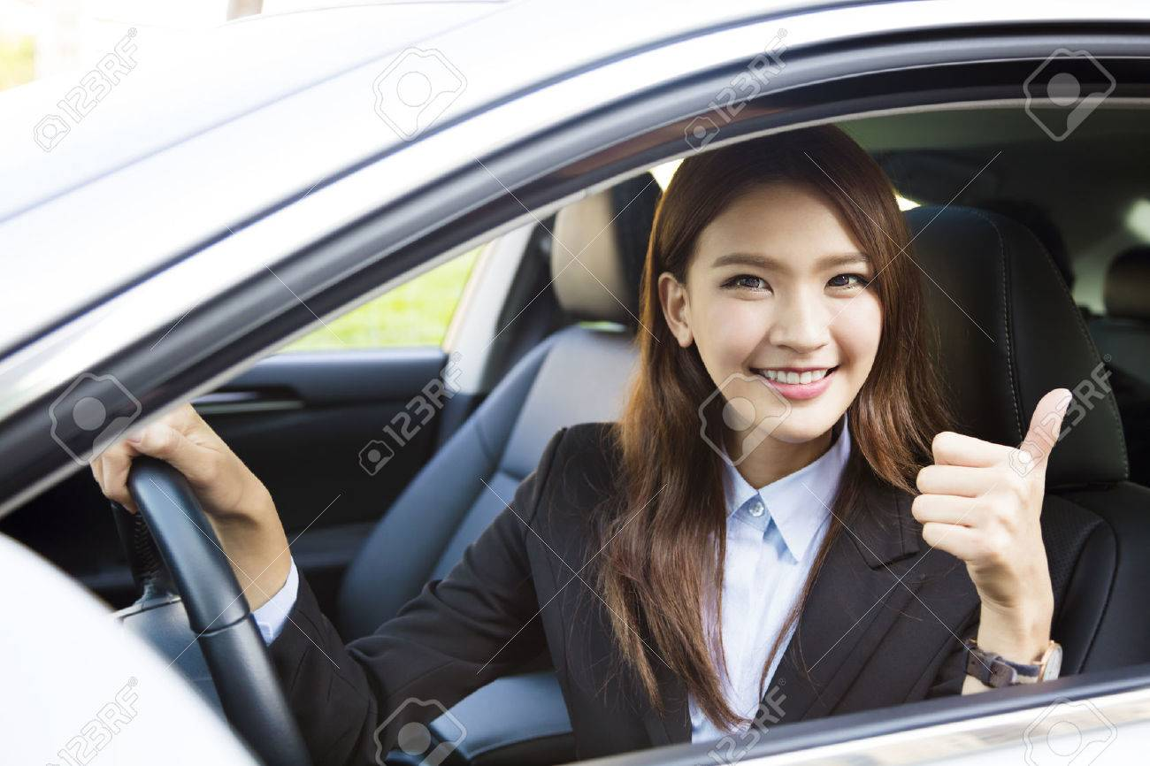 young business woman sitting in car and showing thumbs up - 56373242