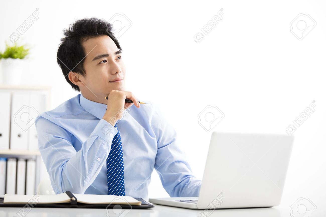 smiling young businessman working on laptop and thinking - 59965448