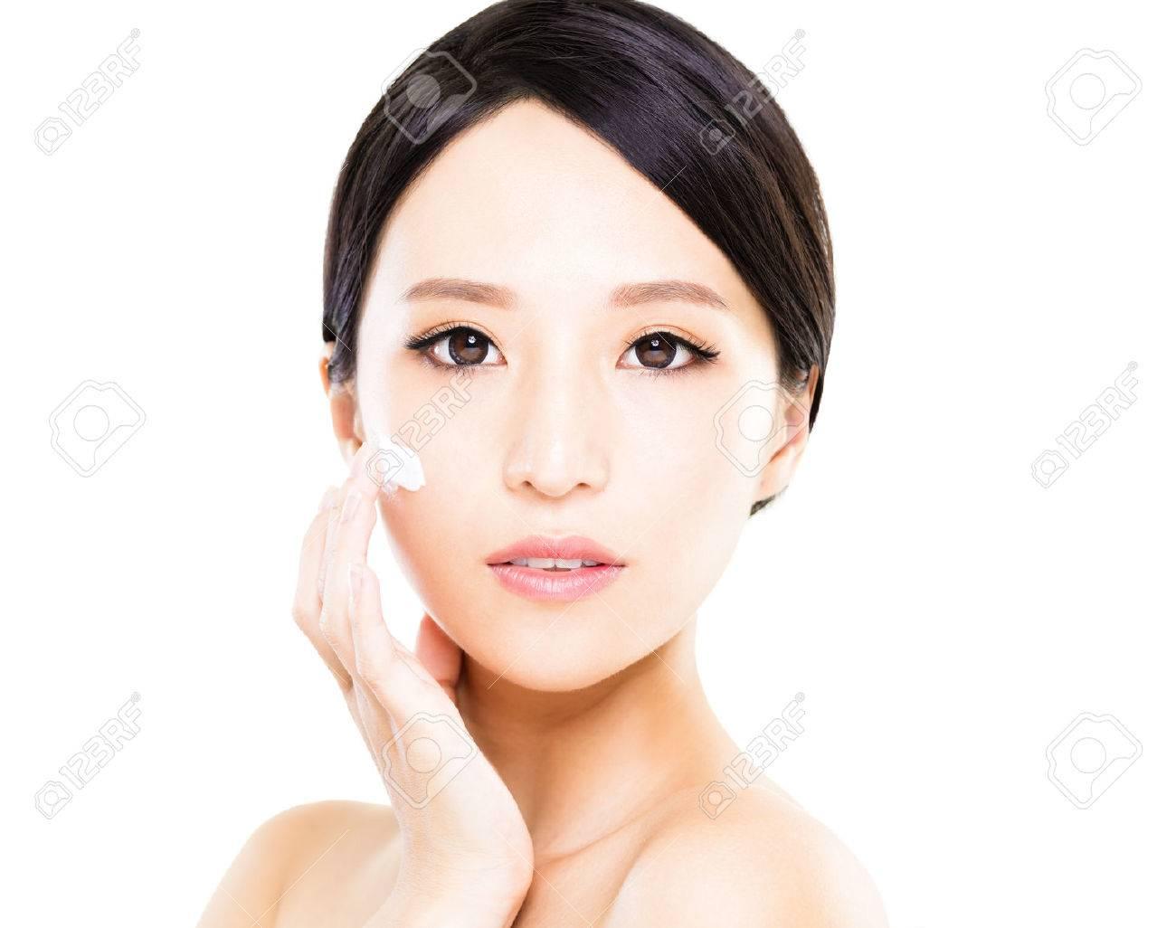 Beautiful women applying moisturizer cosmetic cream on face - 62200501