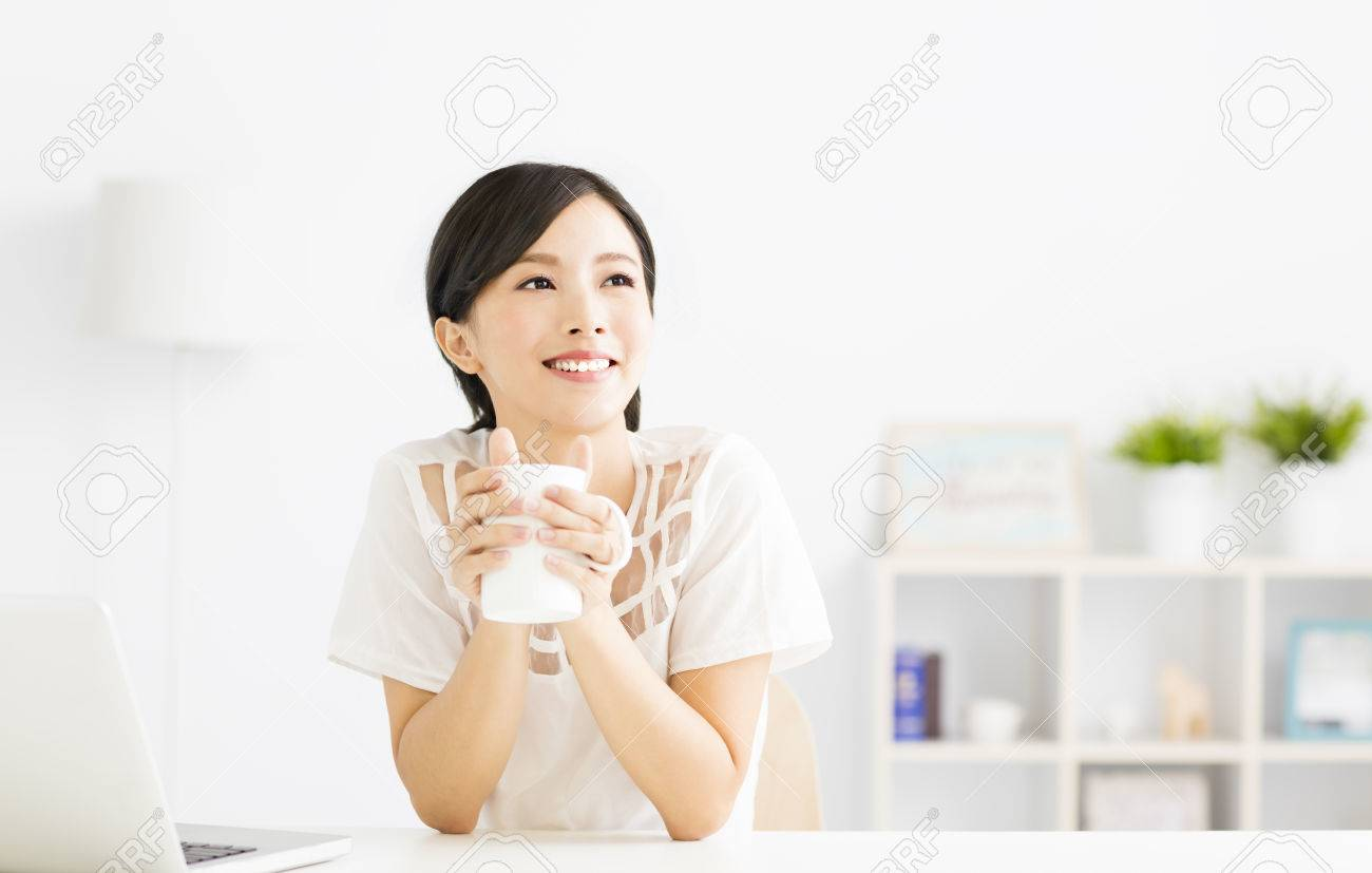 young Woman drinking coffee in living room - 63240517