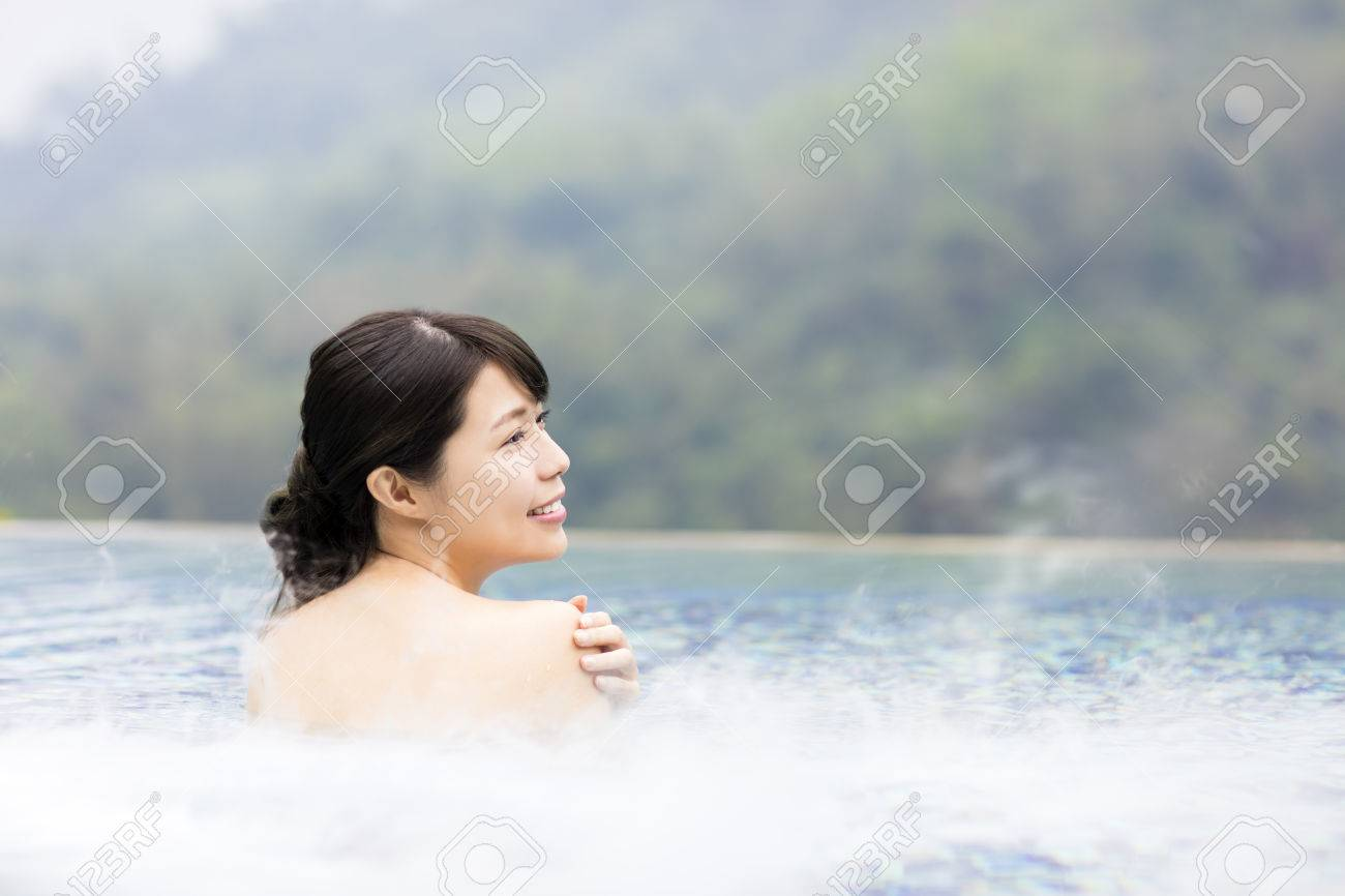 happy young woman relaxing in hot springs - 66159568