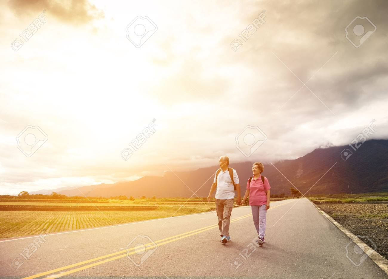 senior couple hiking on the country road - 67438747