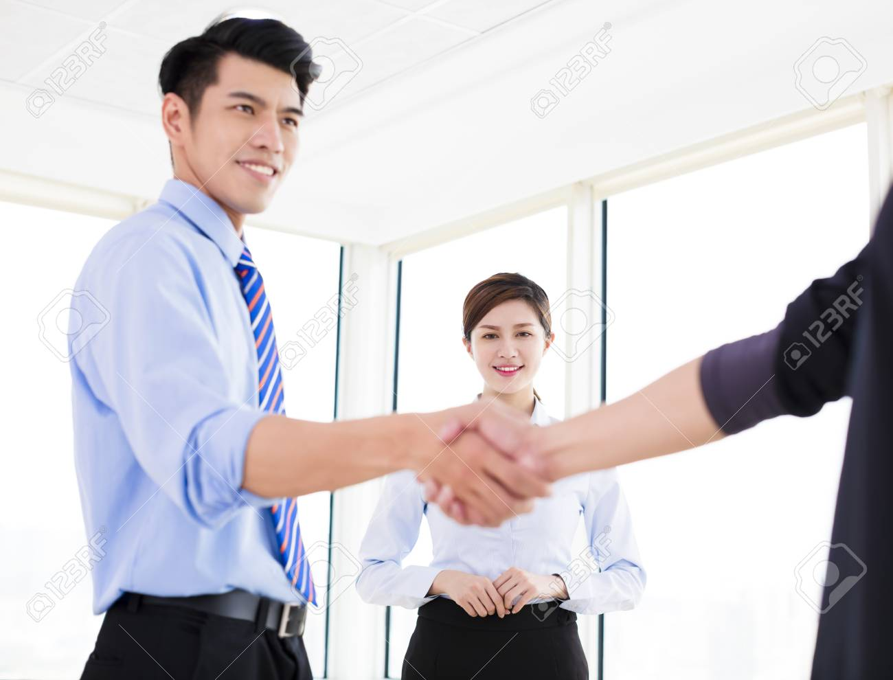 Happy Businessmen Making Agreement And Colleague Standing Near