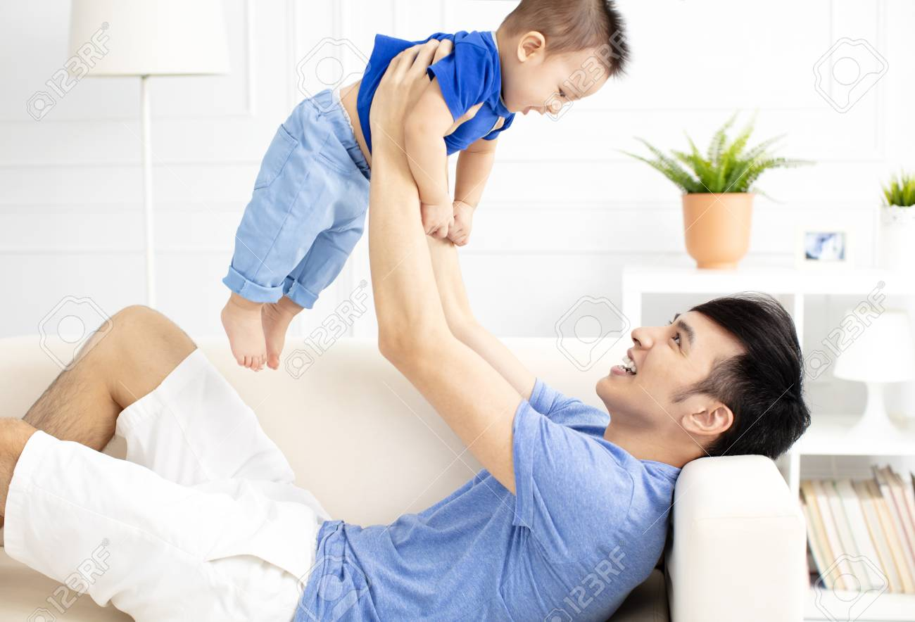 Father And Son Playing On Sofa - 104293291
