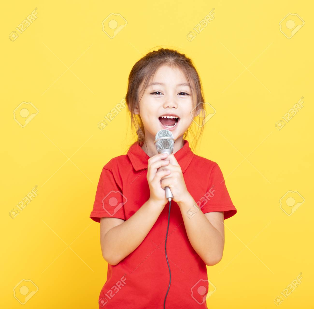 happy little girl singing on yellow background - 107762326