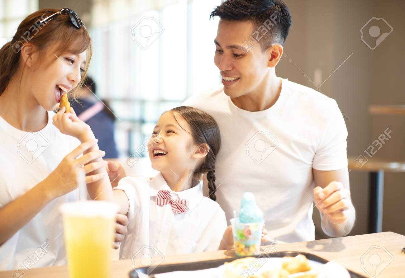 Happy family enjoying dinner in restaurant. - 108467795