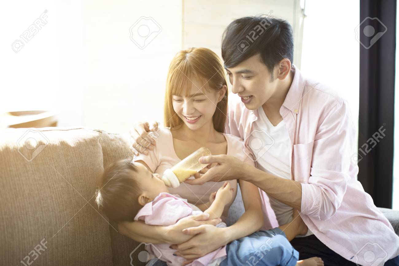 happy father and mother feeding baby from bottle - 110858481
