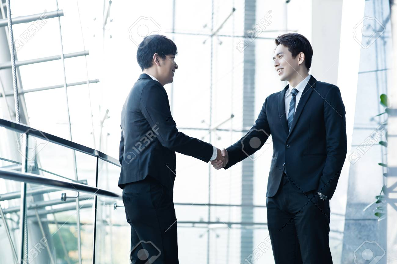 Two confident businessmen shaking hands and smiling - 114883595