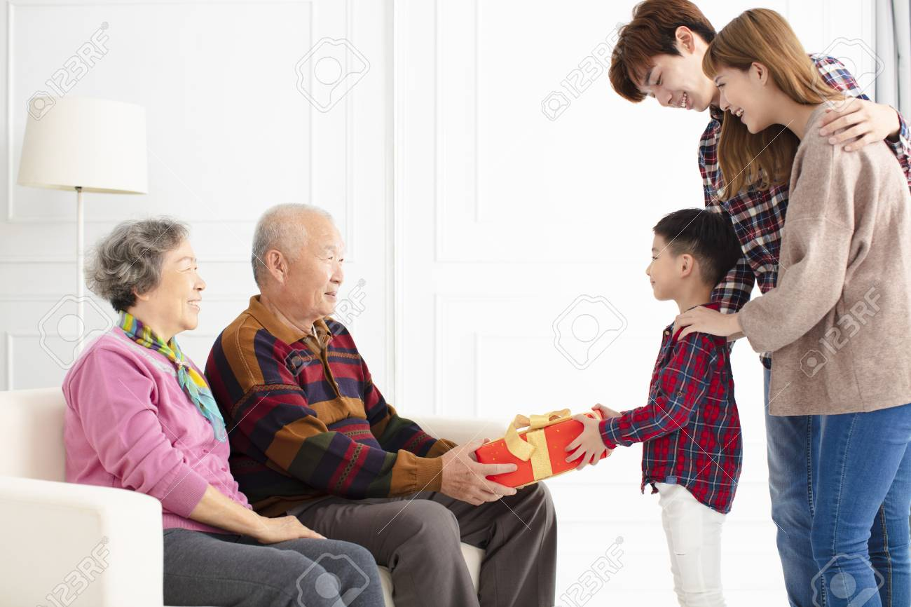 grandchild with parents giving a gift to grandparents - 115369852
