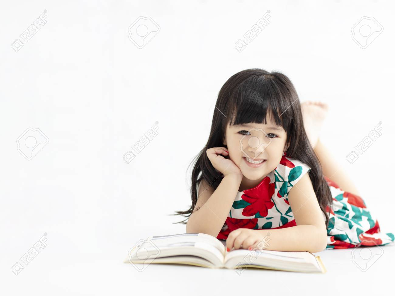 smiling little girl with book lying on the floor - 115661040