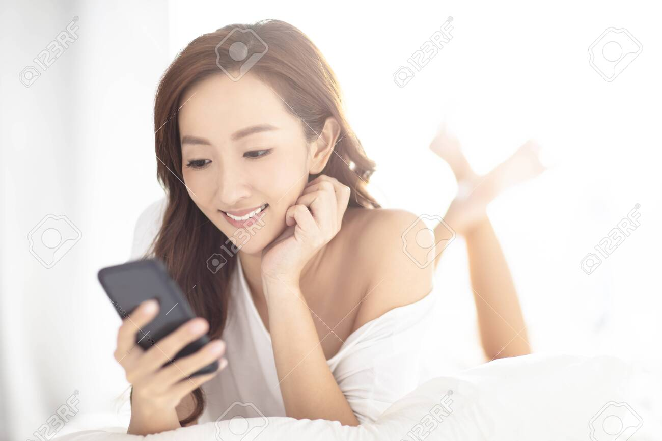 young smiling woman watching mobile phone on bed - 124510003