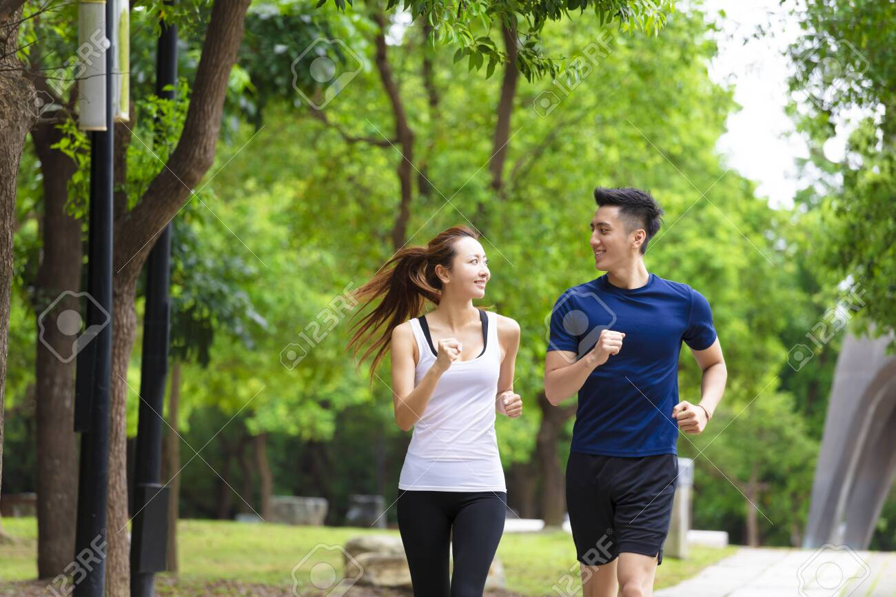 happy young Couple jogging and running in park - 127493174
