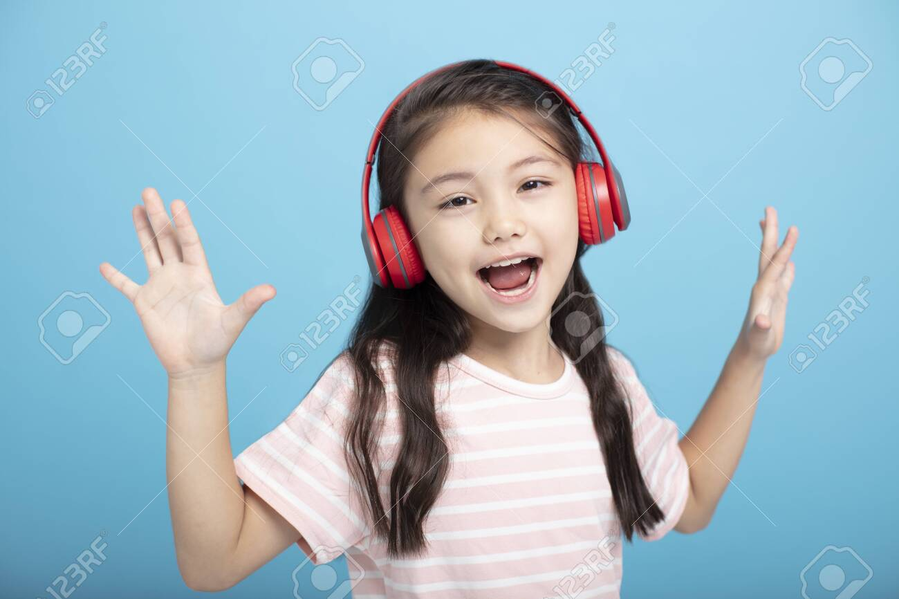 happy little girl with headphones listening and singing song - 133209416